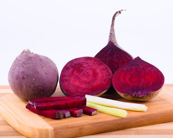 Rödbetor på skärbräda - rödbetsjuice kan förbättra blodfetterna